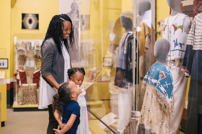 """A Mom and her two children looking into a display case in the """"Cultural Crossroads"""" gallery."""