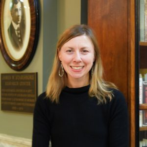Lady with shoulder length blonde hair and brown eyes wearing a black top, and is standing in front of an old fashioned photo and frame James W. Starsmore. Her name is Hillary Mannion, CSPM Archivist