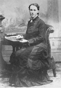 A photo of Julia A. Holmes sitting in a chair.