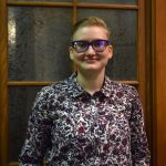 Bust shot of young adult girl with glasses, short blonde hair and in a button down flowered print shirt in reds and blacks with a collar. She is smiling and standing in front of a frosted pane of glass with oak framing.