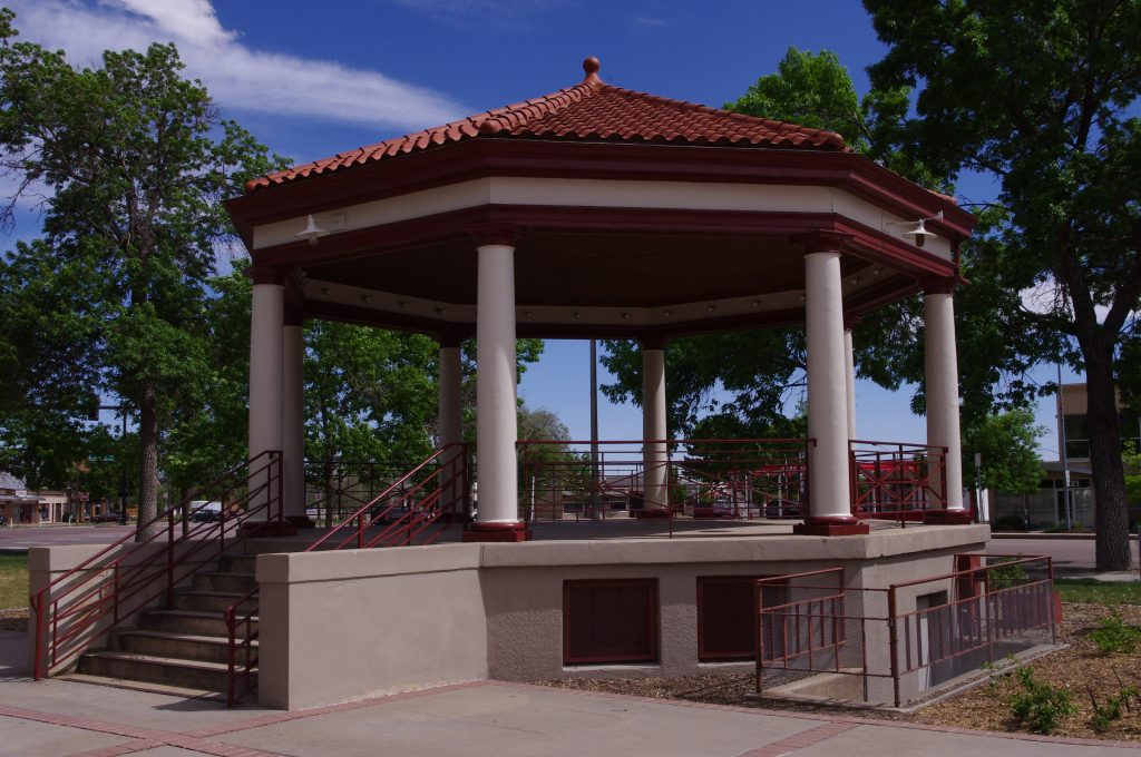 8-sided Gazebo with clay tile roof, round columns supporting canopy and 8 steps leading up to floor of Gazebo.